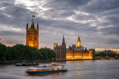 Westminster & BigBen UK. The Palace of Westminster with Elizabeth Tower viewed from across the River Thames under dark clouds Stock Photo