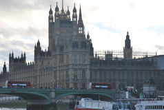 A Westminster bridge and the House of Parliament. A Westminster bridge with crowd of people, usual traffic and typical British buses red, doble-decker buses and Stock Image