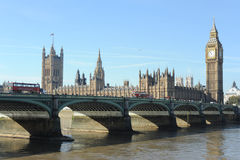 Westminster Bridge and the Houses of Parliament. An image of Parliament taken from the River Thames embankment showing Red London buses going over Westminster Stock Images