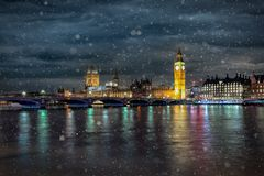 Westminster Bridge, the Parliament and the Big Ben in London on a cold winter night. With falling snow, United Kingdom royalty free stock photo