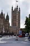 Westminster Palace and London street. Westminster Palace view and pedestrians crossing the street in front of the red bus, London, Great Britain, Europe Stock Photography