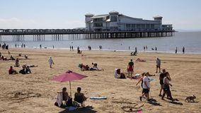 Weston-super-Mare beach and pier Somerset with tourists and visitors enjoying the summer sun stock video footage