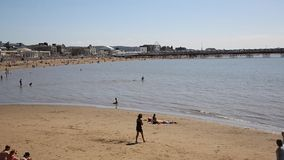 Weston-super-Mare beach and pier Somerset with tourists and visitors enjoying the summer sun PAN stock video footage