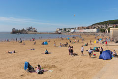 Weston-super-Mare beach Somerset in summer sunshine with tourists and holidaymakers. Beautiful summer sunshine and warm weather drew visitors to the seaside at Royalty Free Stock Images