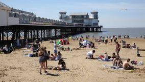 Weston-super-Mare Somerset beach and pier with tourists visitors and holidaymakers enjoying the summer sunshine stock video
