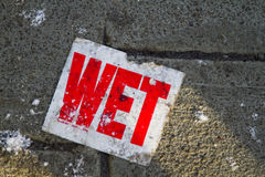 Wet. Sign on  sidewalk with a snow royalty free stock images