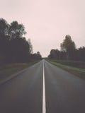 Wet asphalt road with sun reflections. Vintage. Stock Photos