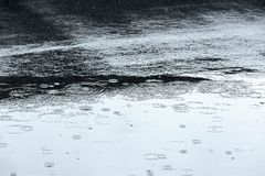 Wet asphalt and water puddle background with reflections Royalty Free Stock Photo