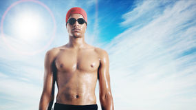 Wet attractive African American swimmer against sky with lens glare Stock Image