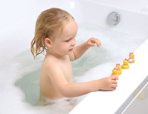 Wet baby girl toddler kid in bathing with soap suds in white bat Stock Photo