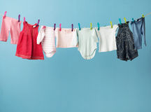 Wet baby's clothes getting dry Stock Images