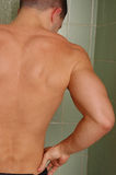 Wet back. Male in a tile shower Royalty Free Stock Images