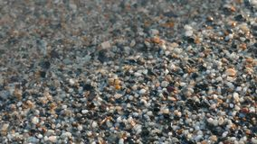 Wet beach sand, close-up. Gray sand under clear water on lake shore stock video