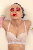 Wet beautiful woman with bright makeup lying in milk Royalty Free Stock Photos