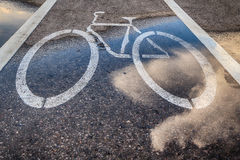 Wet bicycle Lane and reflection of clouds Stock Photo