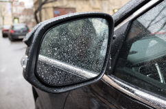 Wet black shining car mirror with raindrops Stock Images