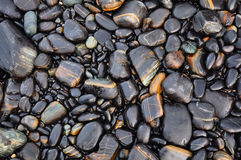The wet black stone. Sea stones on the beach as background.Tarutao National Park,Thailand Royalty Free Stock Images