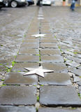 The wet block pavement with stars. Royalty Free Stock Photography