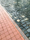 Wet block sidewalk and rough cobblestone road Stock Photo