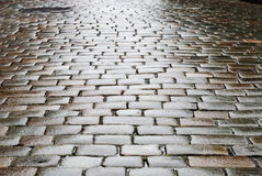 Wet block-stones of sett paving. The wet block pavement is receding into the distance. Focus is on front block-stones Royalty Free Stock Image