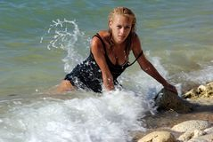 Wet blond kneeling in surf Royalty Free Stock Photos
