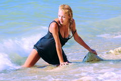 Wet blond kneeling in surf Royalty Free Stock Photo
