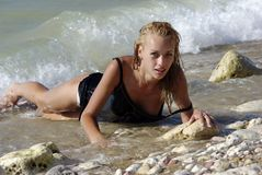 Wet blond laying in surf Stock Photography