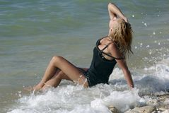 Wet blond sitting in surf Royalty Free Stock Photos