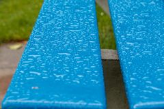 Wet blue bench with large water droplets. After a downpour, this bench in Walenstadt near the Walensee is wet with large drops of water on its freshly painted stock photo