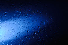 Wet Blue Glass. Wet glass with water droplets in blue light abstract artistic background texture Royalty Free Stock Photos
