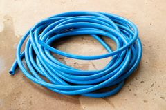 The blue water hose lay down on the floor. The wet blue water hose lay down on the wet concrete floor stock photos
