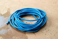 The blue water hose lay down on the floor. The wet blue water hose lay down on the wet concrete floor royalty free stock photo