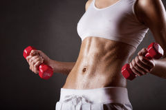 Wet body. Of a young fit woman lifting dumbbells on dark background Royalty Free Stock Image