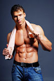 Wet & body. Beautiful man with strong body holding the towel Royalty Free Stock Photos