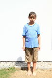 Wet boy. Barefoot little boy in brown shorts and blue t-shirt being wet and standing Royalty Free Stock Photos