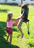 Wet boy and girl on a swing. Wet barefoot little boy in green and small wet barefoot girl in pink on a swing Royalty Free Stock Photo
