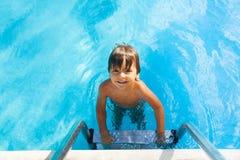 Wet boy holds metallic ladder of swimming pool Stock Photo