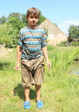 Wet boy by pond. Little boy - kid in wet shorts and t-shirt standing on grass by pond Royalty Free Stock Photos