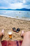 Wet boys feet on beach and sand with cup of beer Royalty Free Stock Photography