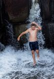 Wet boy in shorts, running in the water, next to a waterfall. A wet boy in shorts, running in the water, next to a waterfall. On a warm summer day, warm and damp Stock Photos