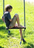 Wet boy on a swing. Wet barefoot little boy in green on a swing Royalty Free Stock Image