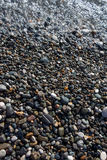 Wet bright shining colored pebble stones and sea wave Stock Photography