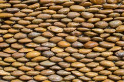 Wet brown pebble stone wall texture Stock Photos