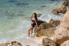 Wet brunette girl in fashionable black swimsuit in rolling sea. Dark haired young woman swimming in a secluded place of wild rocky seashore. Wet brunette girl in Royalty Free Stock Photo