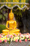 Wet Buddha Statue Flowers Songkran Festival. A shaded Buddha statue covered with flower petals after being cleansed and perfumed for Songkran, Thai New Year in Stock Photos