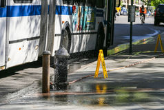 Wet Bus stop. New York City, USA - May 19, 2014: A bus stops in front of an open fire hydrant. Signs warn of a wet floor Royalty Free Stock Photos