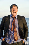 Wet businessman. A color portrait photo of a happy laughing businessman who is soaking wet at the beach Stock Photo