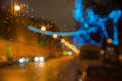 Wet the car window. With the background of the night city lights Stock Images