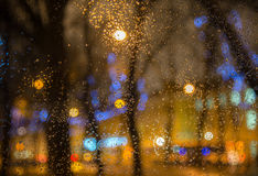 Wet  car window with the background of the night city lights Stock Image