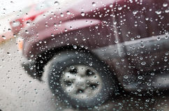 Wet car window with raindrops and a blurred car Stock Image